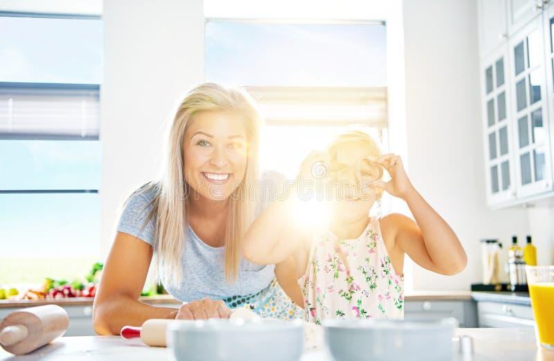 Mulher bonita e menina que jogam na cozinha foto de stock royalty free