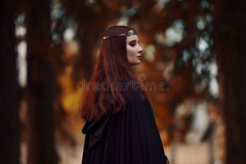Mulher bonita e misteriosa nova nas madeiras, no casaco preto com capa, na imagem do duende da floresta ou na bruxa fotos de stock royalty free