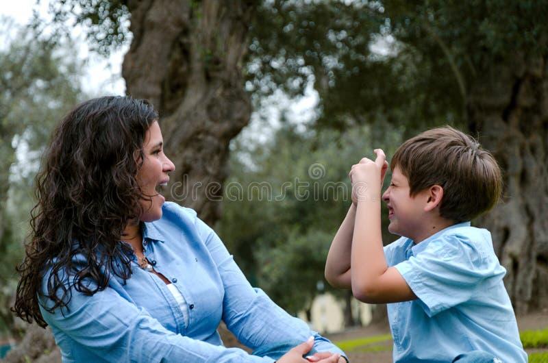 Mulher bonita e seu filho pequeno bonito que olham se, filho que faz a indicação de tomar a imagem da mãe foto de stock royalty free