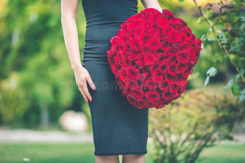 A mulher bonita elegante está vestindo o vestido preto da forma está guardando um ramalhete grande de 101 rosas vermelhas imagens de stock royalty free