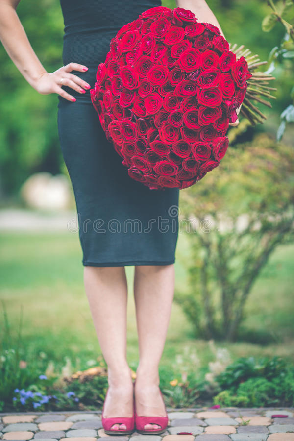 A mulher bonita elegante está vestindo o vestido preto da forma está guardando um ramalhete grande de 101 rosas vermelhas fotos de stock royalty free