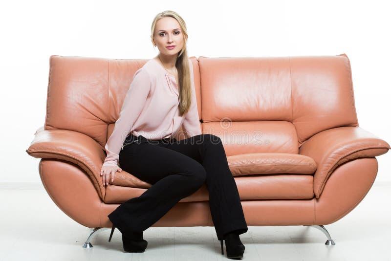 Mulher bonita elegante que senta-se em um sofá a imagem de stock