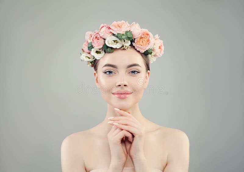 A mulher bonita bonita em flores cor-de-rosa coroa o retrato Modelo saudável dos termas com pele clara e os pregos manicured imagens de stock