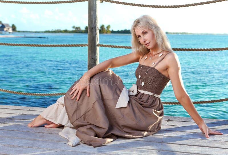 A mulher bonita em um andaime de madeira sobre o mar fotografia de stock