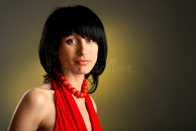 Mulher bonita em um grânulo e em um vestido vermelhos foto de stock
