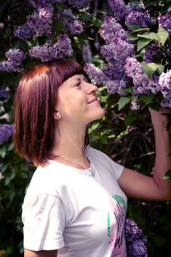 Mulher bonita em um jardim da mola com lil?s de floresc?ncia Fundo da natureza beleza fotos de stock