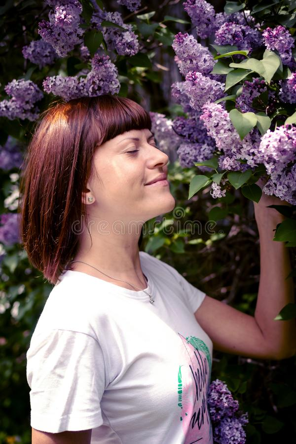 Mulher bonita em um jardim da mola com lil?s de floresc?ncia Fundo da natureza beleza fotos de stock royalty free