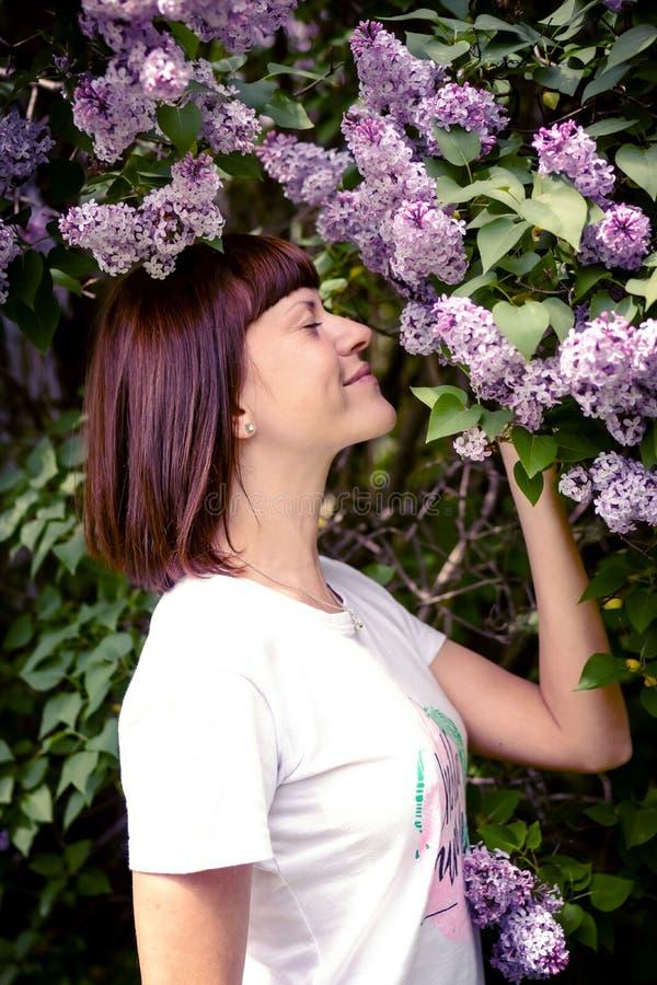 Mulher bonita em um jardim da mola com lil?s de floresc?ncia Fundo da natureza beleza fotografia de stock