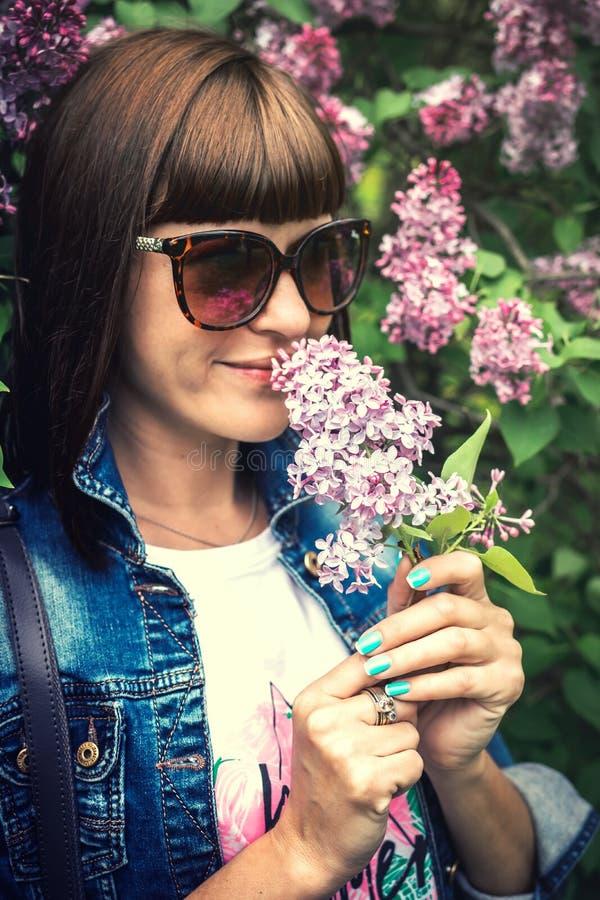Mulher bonita em um jardim da mola com lil?s de floresc?ncia Fundo da natureza beleza fotografia de stock royalty free