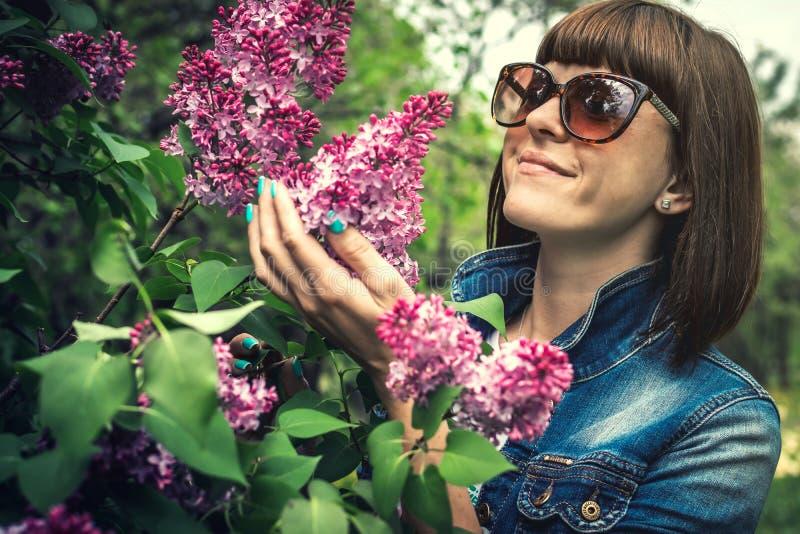 Mulher bonita em um jardim da mola com lil?s de floresc?ncia Fundo da natureza beleza imagens de stock