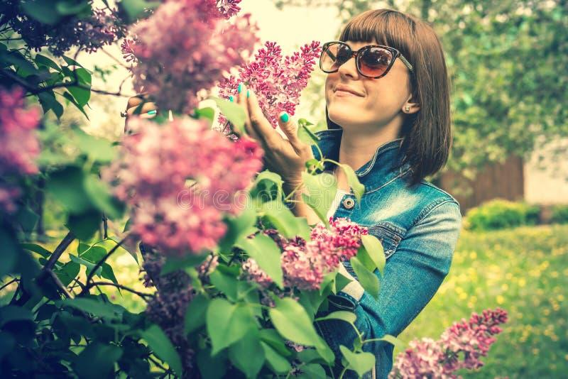 Mulher bonita em um jardim da mola com lil?s de floresc?ncia Fundo da natureza beleza foto de stock royalty free