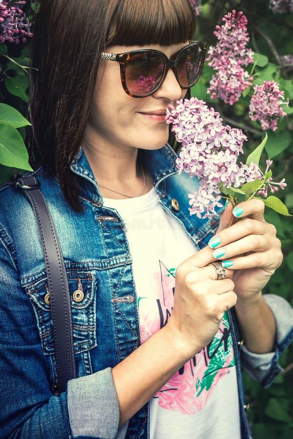 Mulher bonita em um jardim da mola com lil?s de floresc?ncia Fundo da natureza beleza imagens de stock royalty free