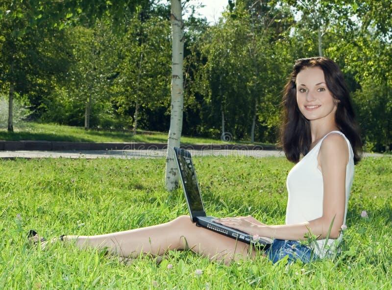 Mulher bonita em um parque com portátil fotos de stock royalty free