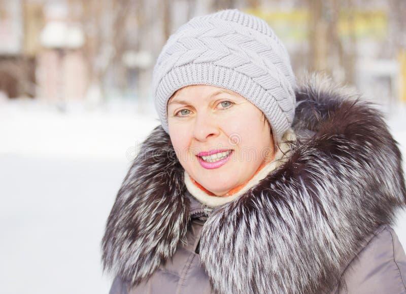 Mulher bonita em um revestimento com colar da pele e um chapéu feito malha foto de stock royalty free