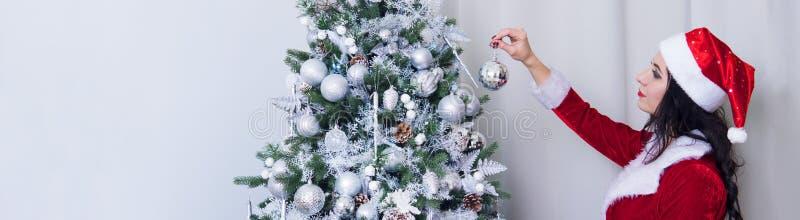 A mulher bonita em um traje 'sexy' de Santa Claus decora as decorações da árvore de Natal em casa A menina pendura uma bola de pr fotos de stock