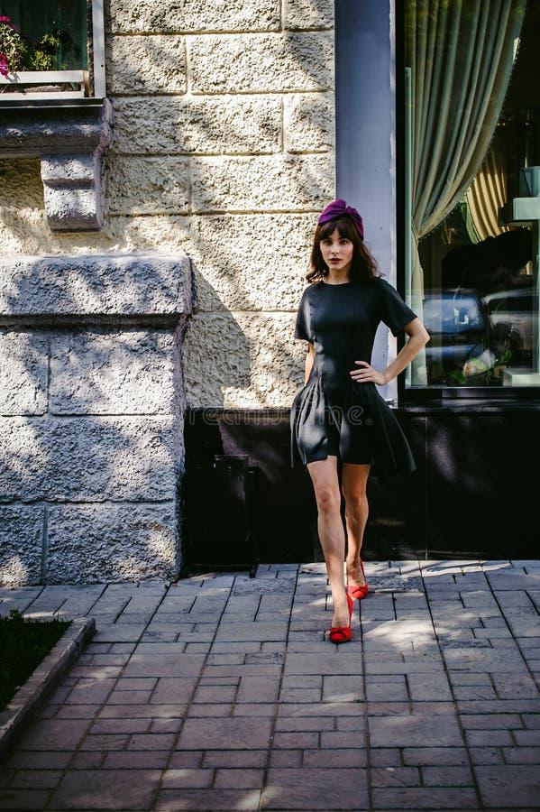 A mulher bonita em um vestido à moda escuro dá uma volta avante Retrato de uma menina elegante imagens de stock