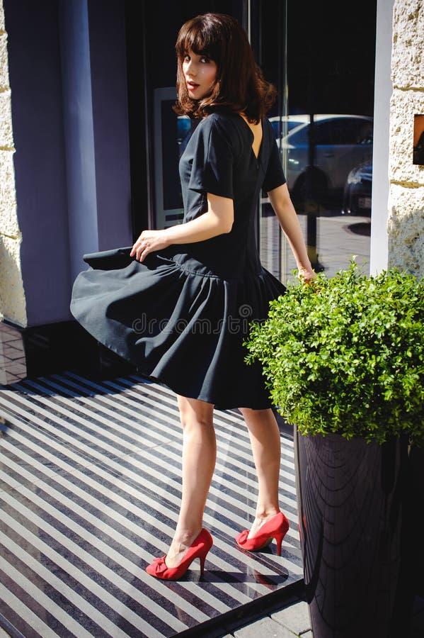 A mulher bonita em um vestido à moda escuro dá uma volta avante Retrato de uma menina elegante foto de stock