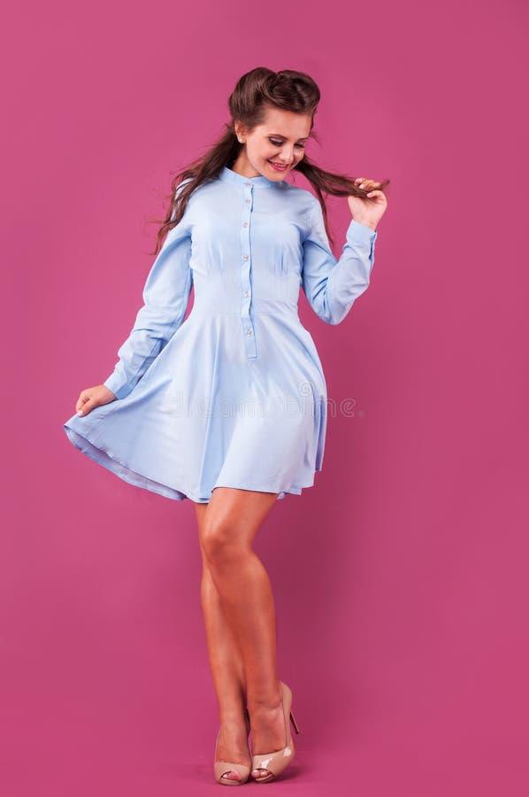 Mulher bonita em um vestido azul no fundo cor-de-rosa no estúdio foto de stock royalty free