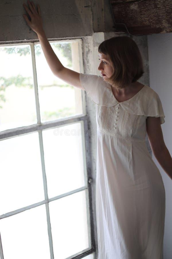 Mulher bonita em um vestido branco na luz da janela foto de stock royalty free