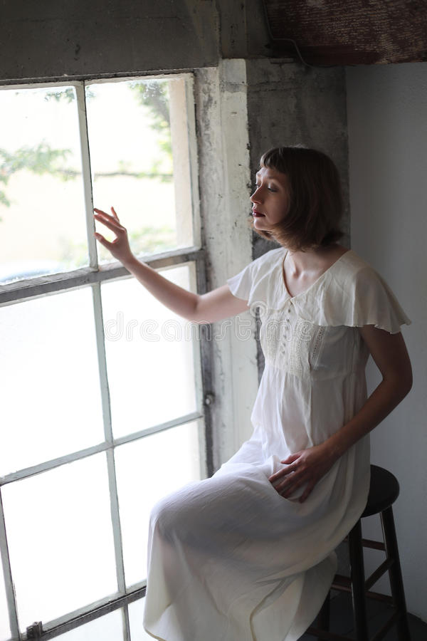 Mulher bonita em um vestido branco na luz da janela fotos de stock