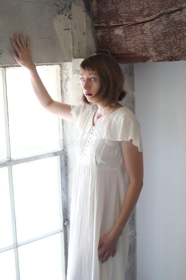 Mulher bonita em um vestido branco na luz da janela fotografia de stock