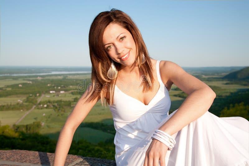 Mulher bonita em um vestido branco que levanta ao ar livre fotos de stock