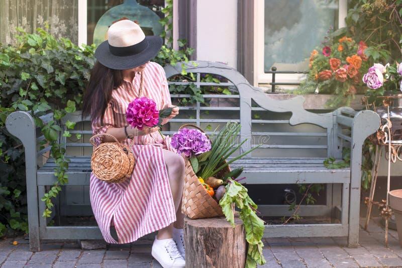 A mulher bonita em um vestido com compras, senta-se em um banco na rua da cidade Uma grande cesta dos vegetais e das flores no imagem de stock