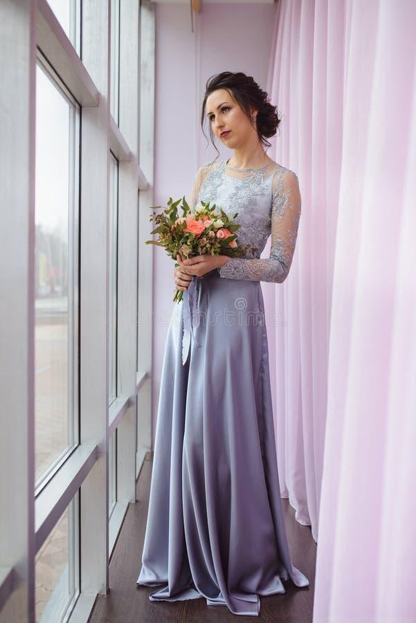 A mulher bonita em um vestido da ameixa que levanta com um ramalhete das rosas aproxima a janela imagens de stock royalty free