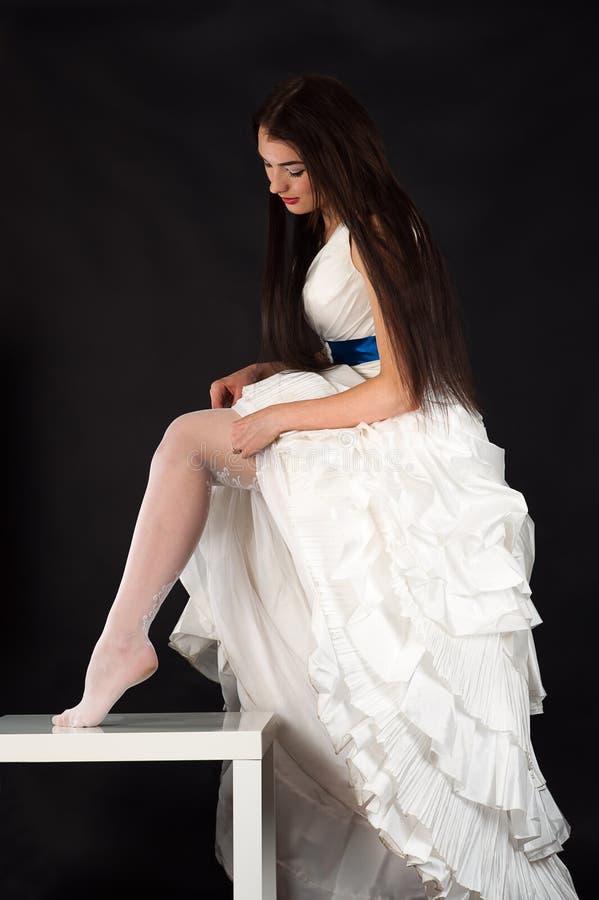 A mulher bonita em um vestido de casamento endireita meias foto de stock royalty free