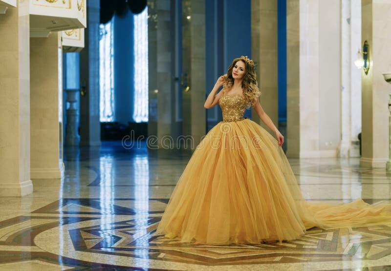Mulher bonita em um vestido longo e em uma coroa dourada no grande imagem de stock