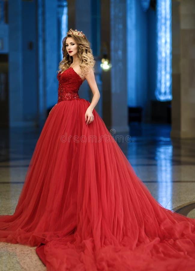 Mulher bonita em um vestido longo vermelho e em uma coroa dourada na GR imagens de stock royalty free