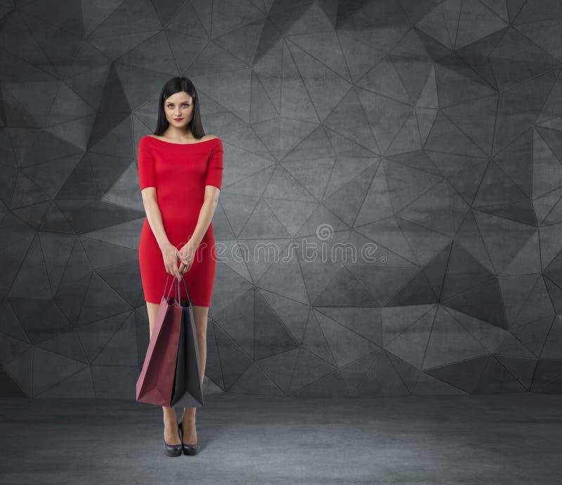 A mulher bonita em um vestido vermelho está guardando sacos de compras extravagantes Fundo contemporâneo imagem de stock