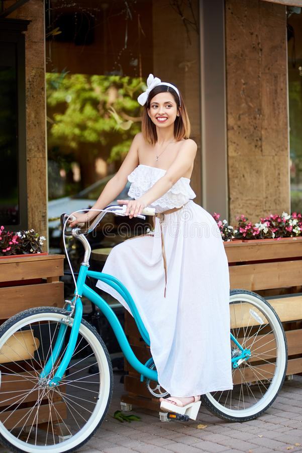 Mulher bonita em uma bicicleta do vintage perto do café da rua do verão fotografia de stock