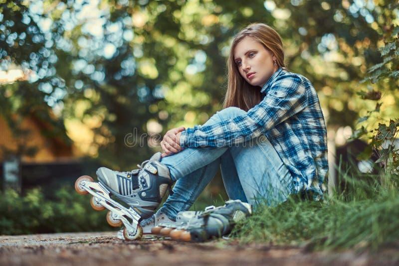 Mulher bonita em uma camisa e nas calças de brim do velo que descansam após a patinagem de rolo foto de stock