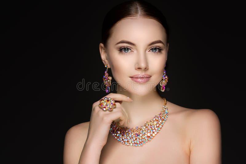 Mulher bonita em uma colar, em brincos e em anel Modelo na joia foto de stock