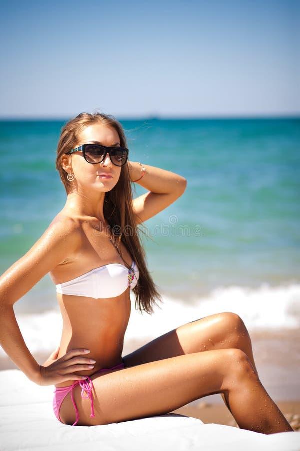 Mulher bonita em uma praia em uma sala de estar do chaise fotos de stock