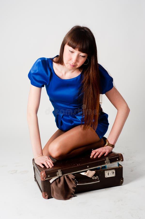A mulher bonita embala a roupa na mala de viagem de couro velha fotos de stock royalty free
