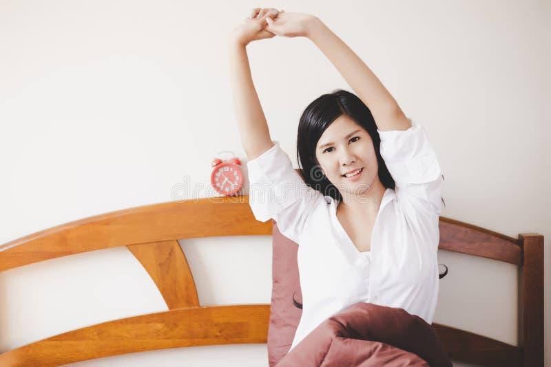 Mulher bonita encantador do retrato A menina bonita atrativa está acordando na manhã e está esticando seus braços e corpo imagens de stock