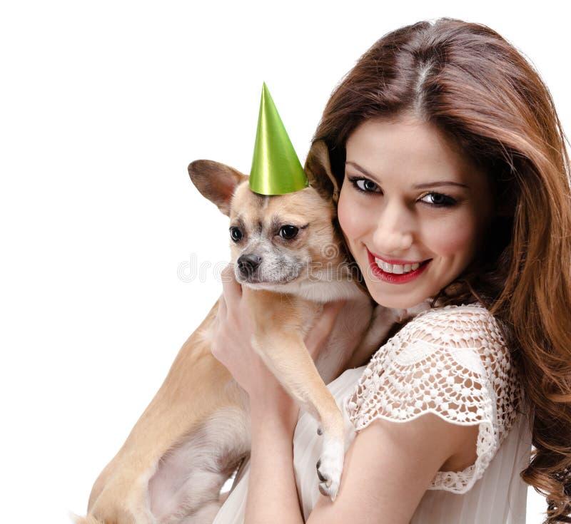 A mulher bonita entrega um cão pequeno straw-colored imagem de stock royalty free