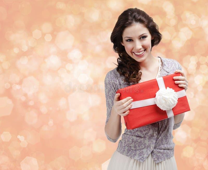 A mulher bonita entrega um presente com curva branca imagem de stock
