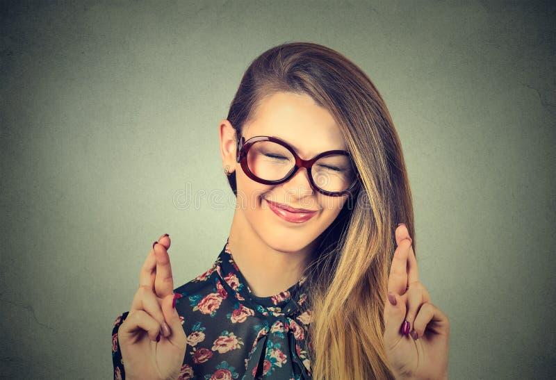 Mulher bonita esperançosa que cruza seus dedos, olhos fechados, esperando, pedindo melhor imagem de stock royalty free