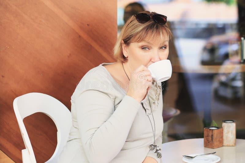 A mulher bonita está bebendo o café no café foto de stock royalty free
