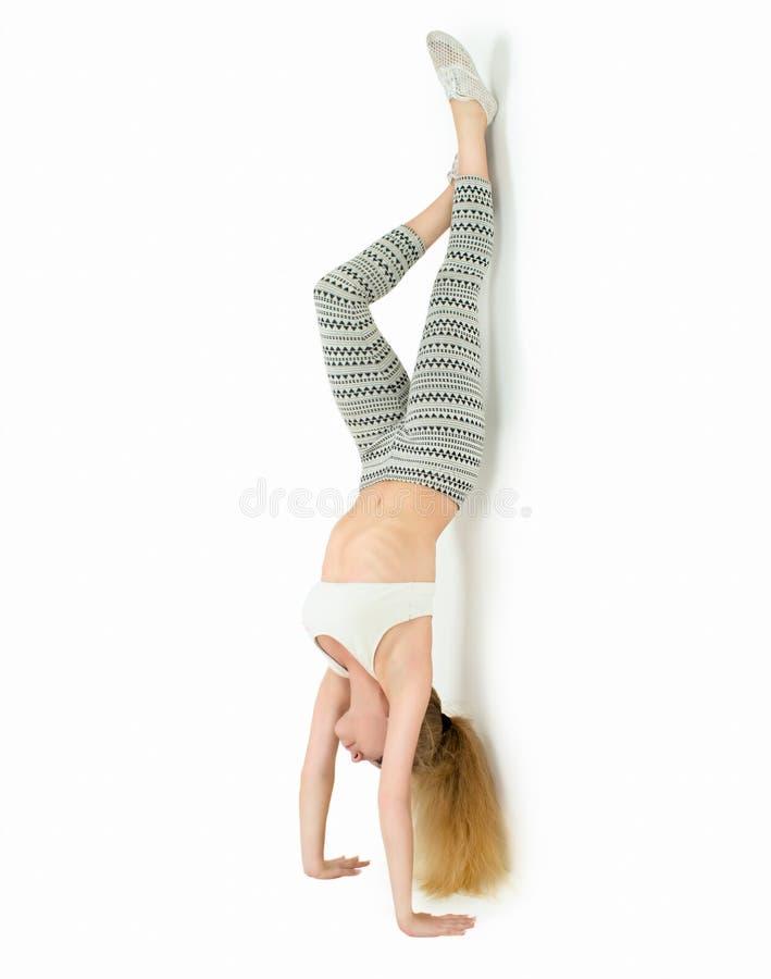 A mulher bonita está estando nas mãos, guardando os pés no ar Isolado sobre o fundo branco fotos de stock
