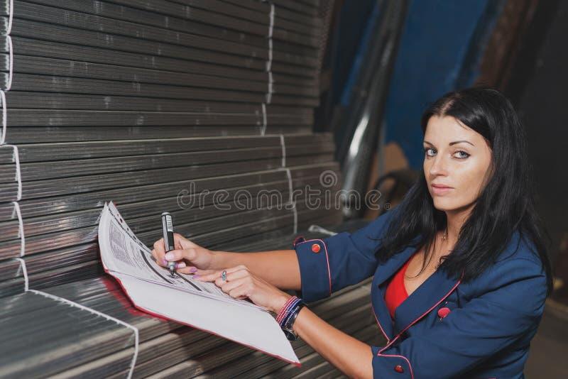 A mulher bonita está gravando e está explicando de perfis do metal dentro foto de stock