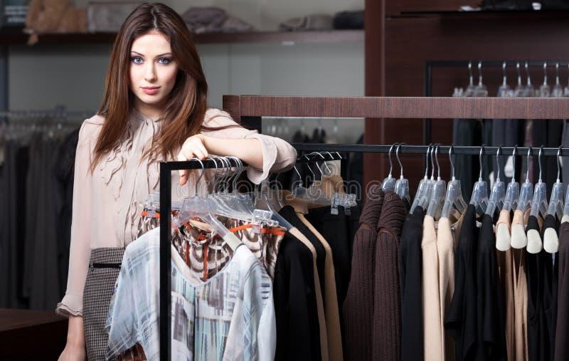 A mulher bonita está na loja da roupa imagem de stock
