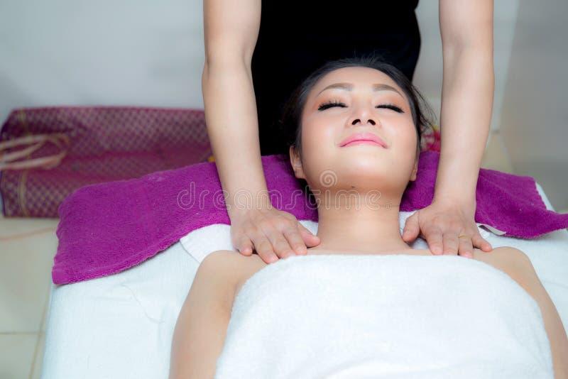 A mulher bonita está obtendo uma massagem facial no salão de beleza dos termas foto de stock