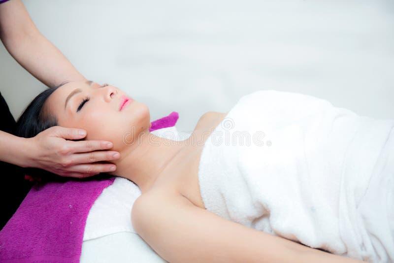 A mulher bonita está obtendo uma massagem facial no salão de beleza dos termas fotos de stock royalty free