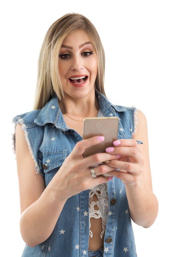A mulher bonita está olhando a tela do telefone celular Ela surpr do ` s foto de stock