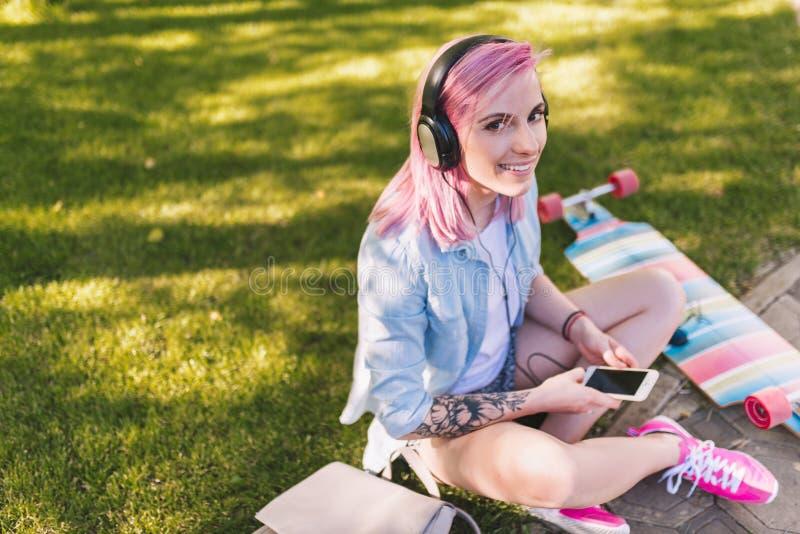 Mulher bonita europeia do moderno na moda com cabelo cor-de-rosa nos fones de ouvido que escuta a música do telefone esperto que  foto de stock