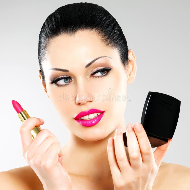 Mulher bonita que aplica o batom cor-de-rosa nos bordos fotos de stock royalty free